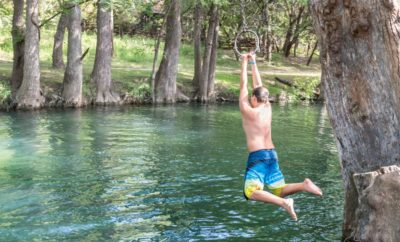 Child swinging into Blue Hole Swimming Hole in Wimberly Texas