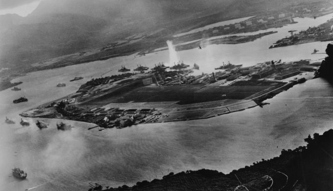 Photograph taken from a Japanese plane during the torpedo attack on ships moored on both sides of Ford Island. View looks about east, with the supply depot, submarine base and fuel tank farm in the right center distance. A torpedo has just hit USS West Virginia on the far side of Ford Island (center).