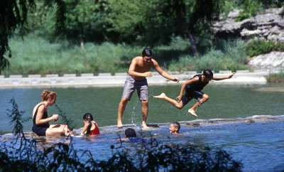 A family with small children swimming in the river. One of the boys is jumping into a deeper part of the river. The mother is sitting on rocks in the water helping a young girl on to the rocks.
