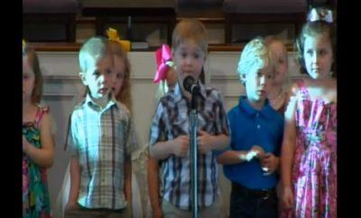 Boy singing Bible books at church