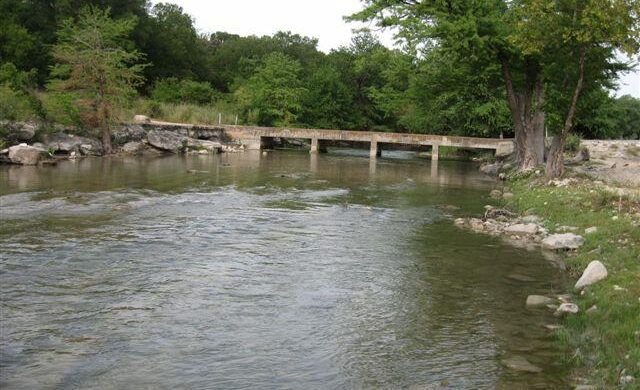 A river that has a concrete bridge in the center of the picture. The banks get wider with more tress and more banks as you look past the bridge. Going past the bridge shows that you are moving deeper into the woods. In the front you can see that there is a dirt road very close to the banks showing easy road access to the bank as well as the bridge.