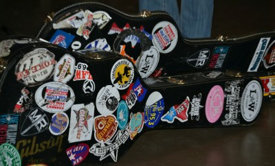 Guitar cases with various stickers from radio stations, music venues and artists