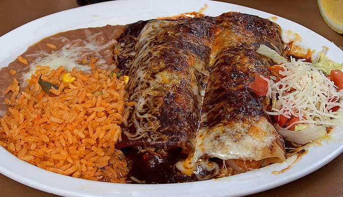 Enchiladas with a side of ubiquitous rice and beans are common Tex-Mex cuisine fare