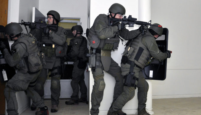 Police Officer SWAT team making entry into building