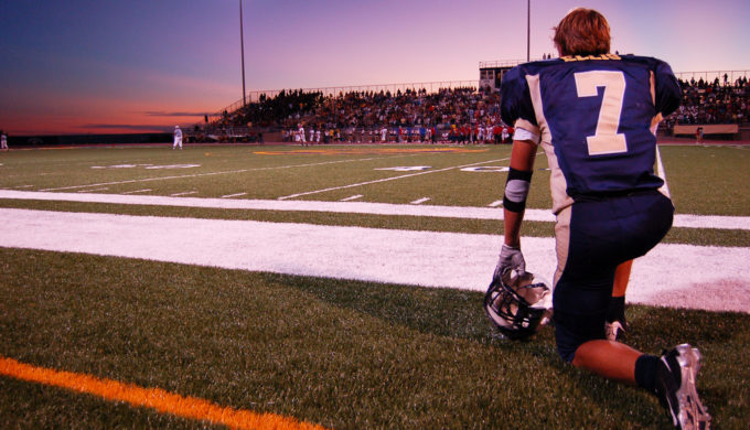 Football Player knealing on sidelines