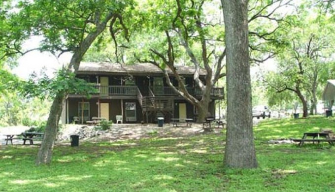 A brown lodging building with several rooms. In front of the building are picnic table, chairs, bar-b-que grills, and several trees. The picture reflects that the grounds to this location are wide and open with green grass.