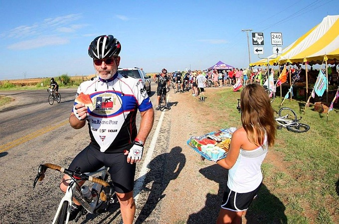 Volunteer offering watermelon to a cyclist.