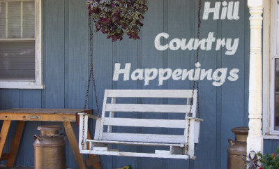 Hill Country Happenings logo painted on blue barn wall with white porch swing