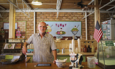 David Brown poses behind counter at Happy Scoops Ice Cream