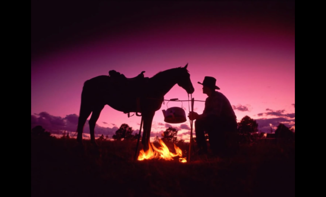 Silhouette of cowboy and his horse in front of a campfire at sunset