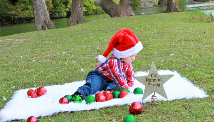 toddler boy playing with Christmas balls outside on a rug