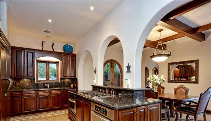 The Arched Theme Continues In Spacious Kitchen Looking Into Dining Room With Wood Beamed Ceiling Accents