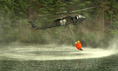 Firefighting Army National Guard UH-60 Black Hawk helicopter dips a Bambi Bucket into a lake for water to fight a wildfire