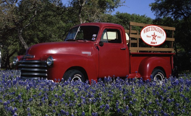 Shot of old time red Ford with Whittington's sign in a field of bluebonnets