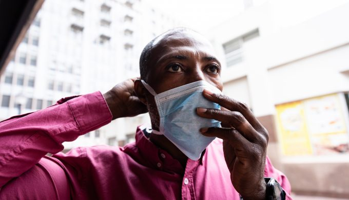 African American man out and about in the city streets during the day, putting on a face mask against air pollution and covid19 coronavirus.