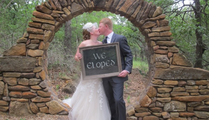 bride and groom with elopement sign