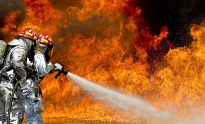 Firefighters spraying water Firefighter's Prayer on flames