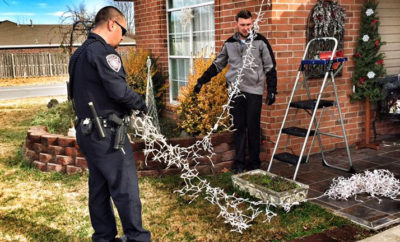 Two Centerton Officers working together to hang Christmas lights