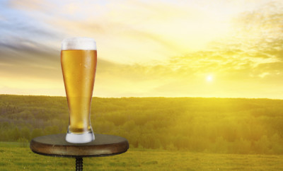 Glass of beer on a table with sunset in the distance shining through