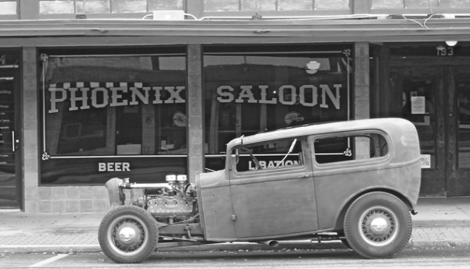 Black and white photo of vintage vehicle parked in front of the Phoenix Saloon in New Braunfels, Texas