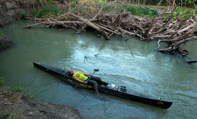 Exhausted participant of the Texas Water Safari lays in canoe floating on the river