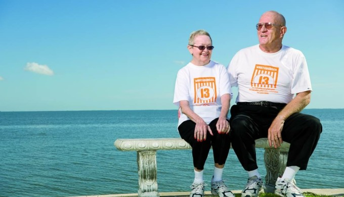 Carol and Karl Hoepfner sitting in front of the Gulf Coast wearing Whataburger tshirts