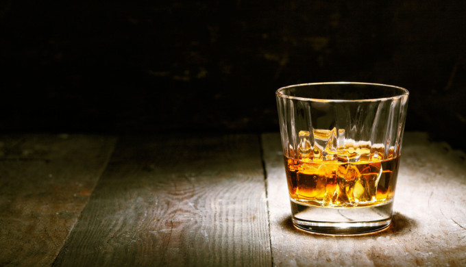Glass of amber colored whiskey spotlighted on wooden table