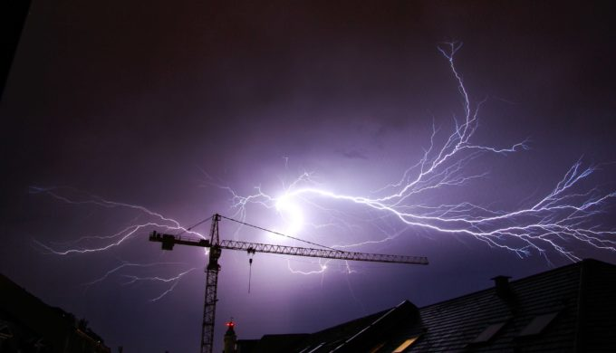 lightning crackling over a crane in the night sky
