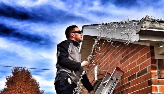 Centerton, AR officer on ladder hanging Christmas Lights