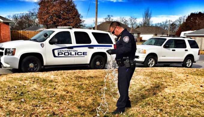Centerton, AR Police Officer sorting out a cord of Christmas Lights