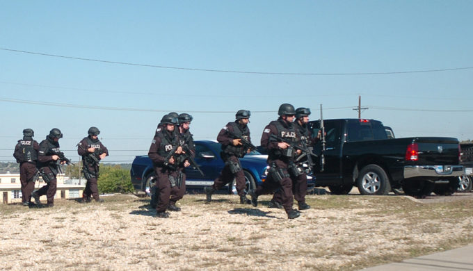 SWAT team members approach a building with a gunman inside.