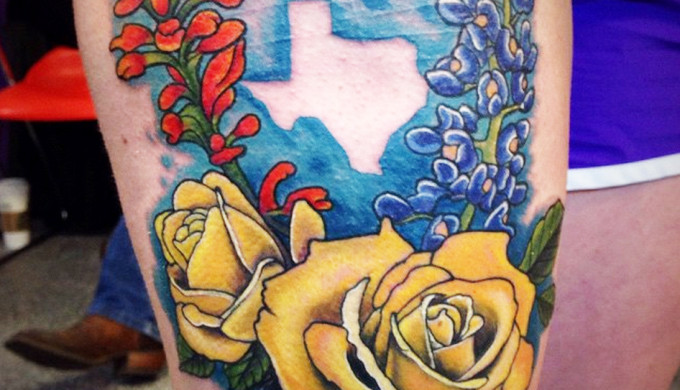 Vibrant tattoo of Texas wildflowers with a silhouette of Texas against blue background